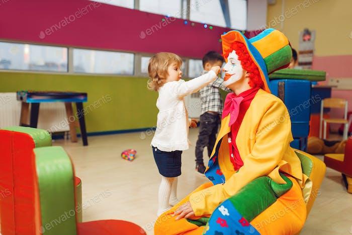 Lustige Clown-Spiel mit kleinen Mädchen im Kindergarten