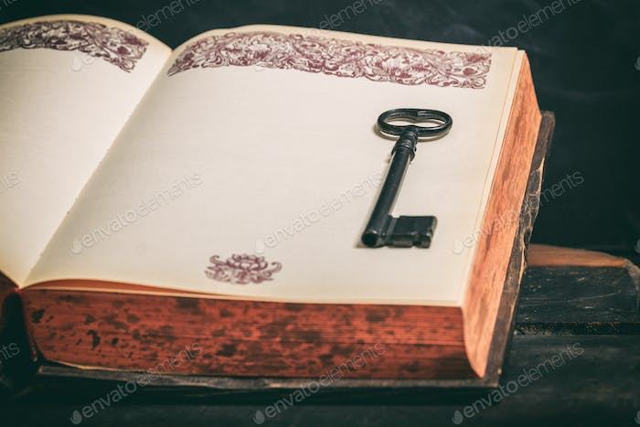 Key on a vintage book on wooden background