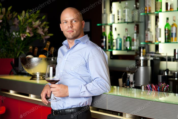 young handsome man waiting next to the bar