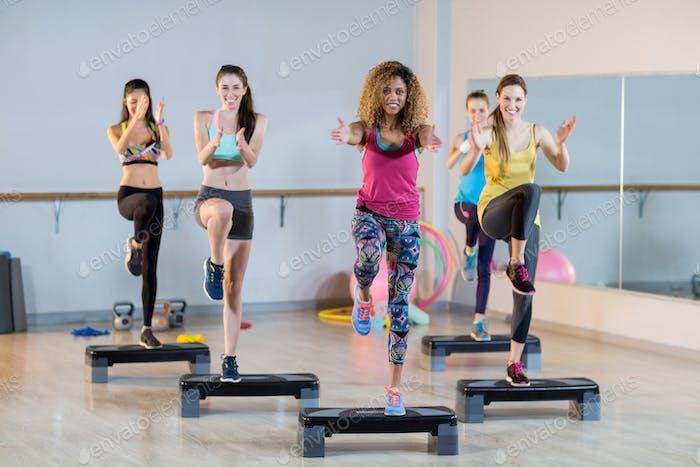 Gruppe von Frauen, die auf aerobe Stepper trainieren