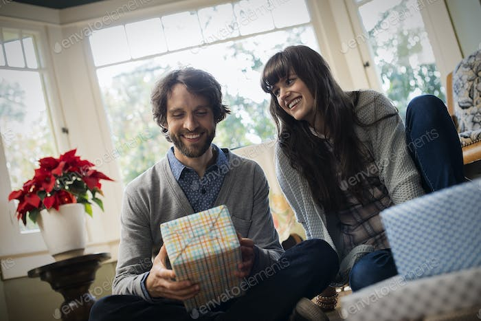 A couple on a sofa, exchanging wrapped presents.