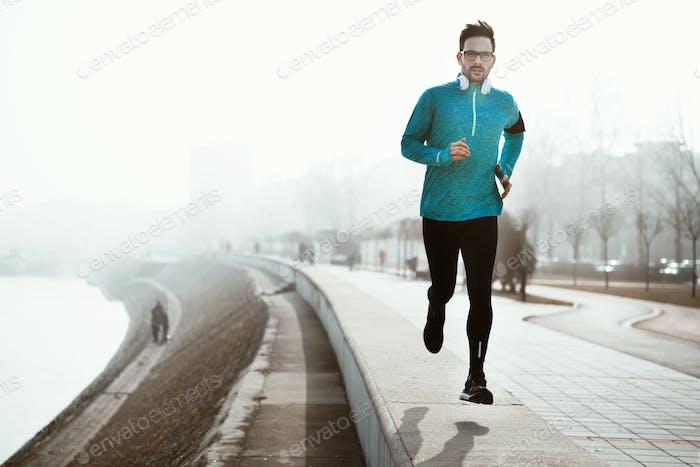 Runner ejercitando al aire libre en niebla y Clima brumoso para mantenerse activo