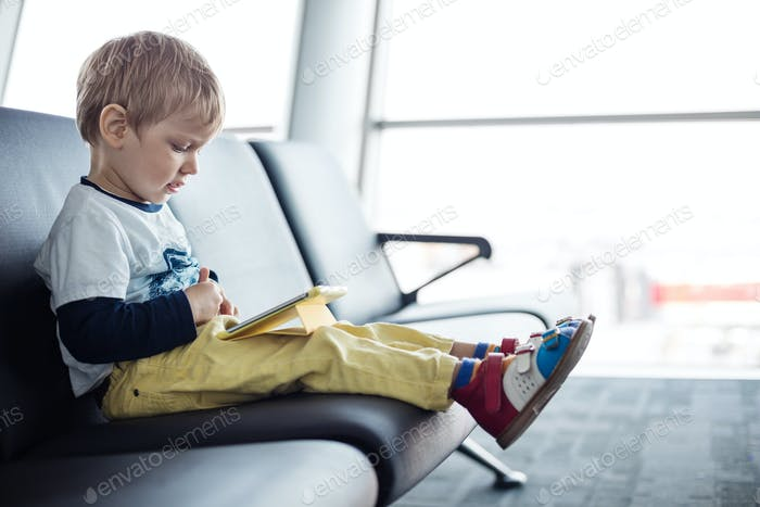 Kleiner Junge sitzt in einer Abflughalle am Flughafen und mit seinem Tablet