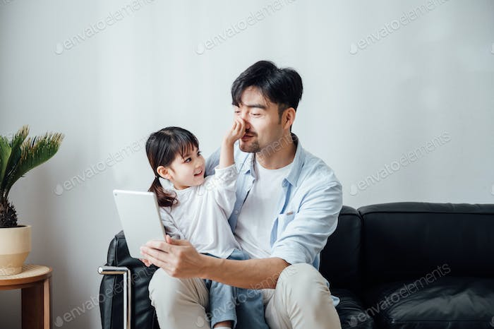 Father and daughter using ipad together at home