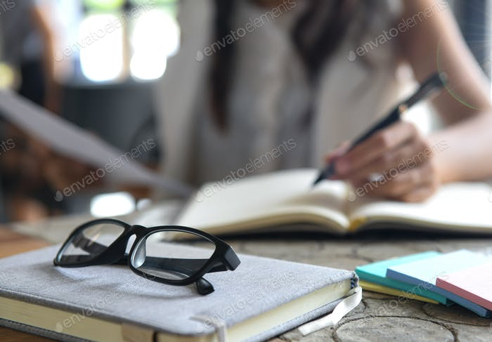 Glasses placed on a notebook, Background blurred women are checking graphs and writing notes.