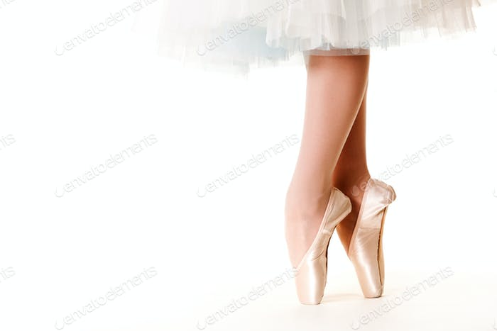 Legs of ballerina woman in white tutu and pointe shoes over white background