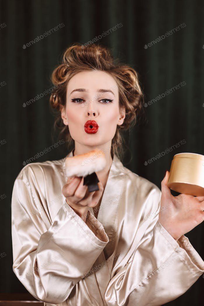 Young beautiful woman with wavy hairstyle and red lips in silk r