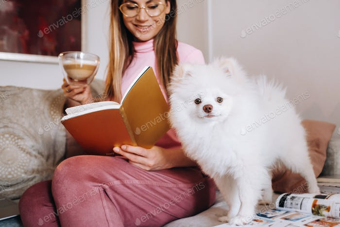 a girl in pajamas at home reads a book with her dog Spitzer, the Dog and its owner are resting on