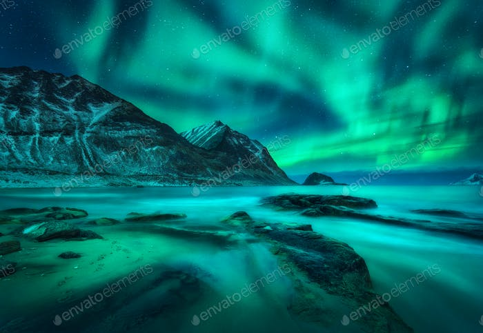 Aurora borealis over snowy mountains, sea coast with sandy beach
