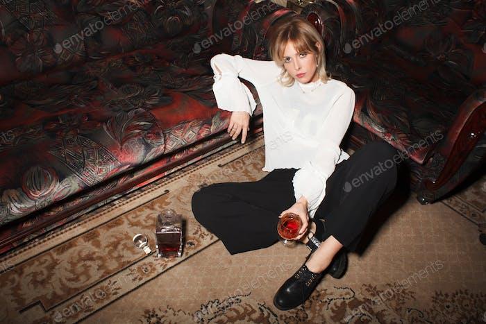 fashionable woman drink cognac in luxury interior
