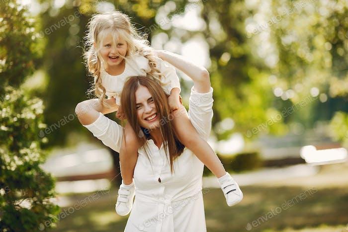 Mutter mit kleiner Tochter spielen in einem Sommerpark