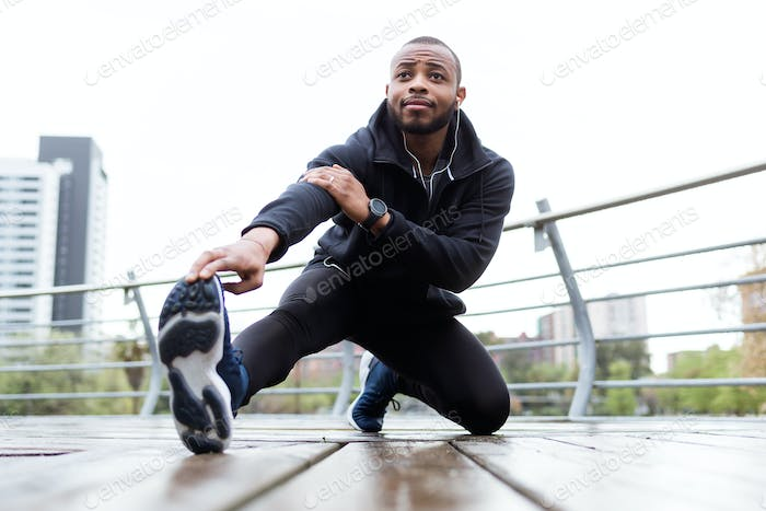 Fit and sporty young man doing stretching in the city.