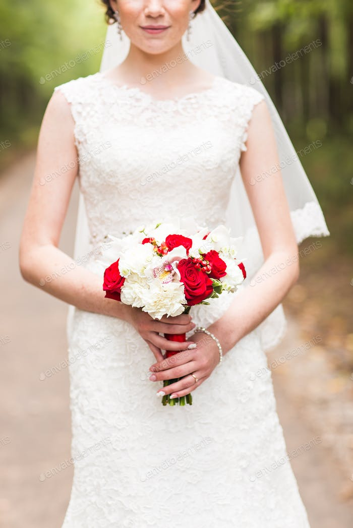 Beautiful bride with wedding bouquet outdoors in a park.