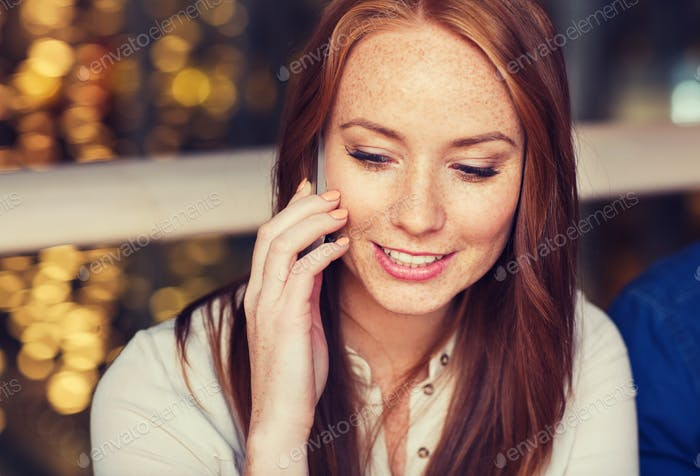 happy woman calling on smartphone at restaurant