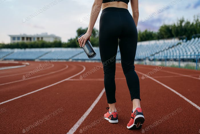 Female runner, back view, training on stadium