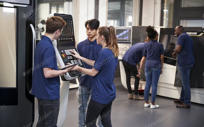 Engineer Showing Apprentices How To Use CNC Tool Making Machine