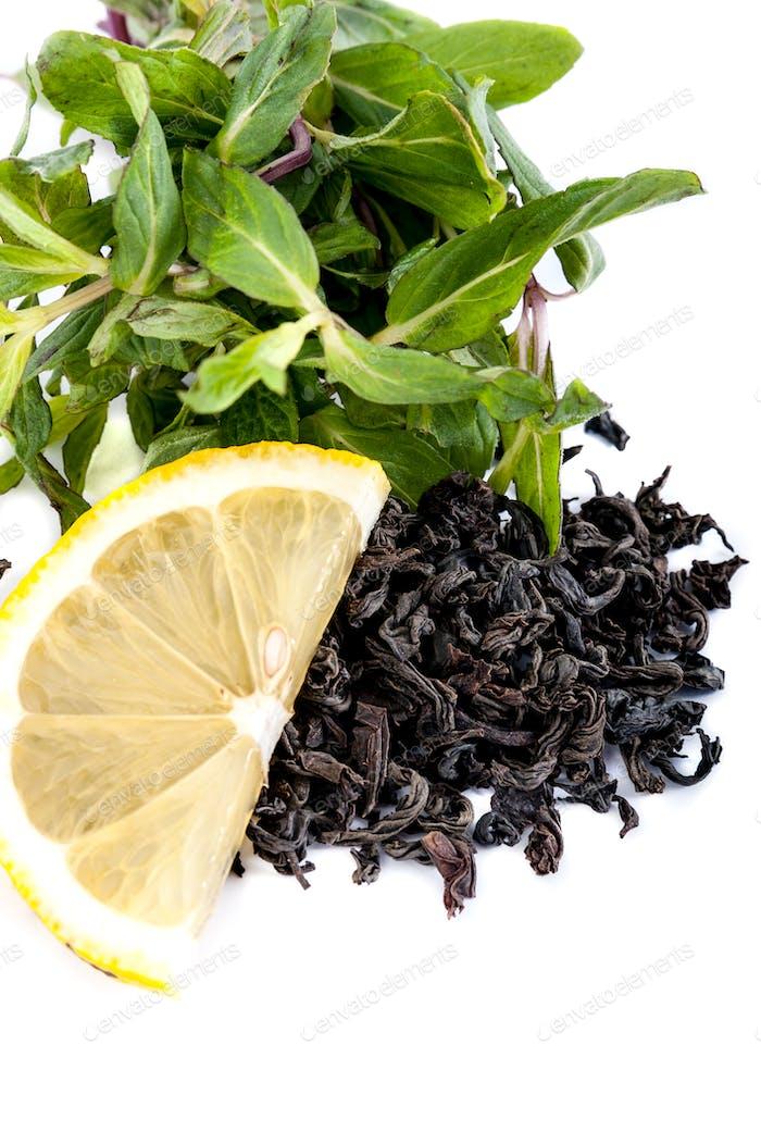 A large leaf black tea, fresh mint and a slice of lemon on a whi