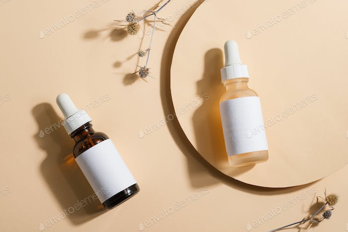 Mockup cosmetic bottles with a dropper on a beige background with bright sunlight