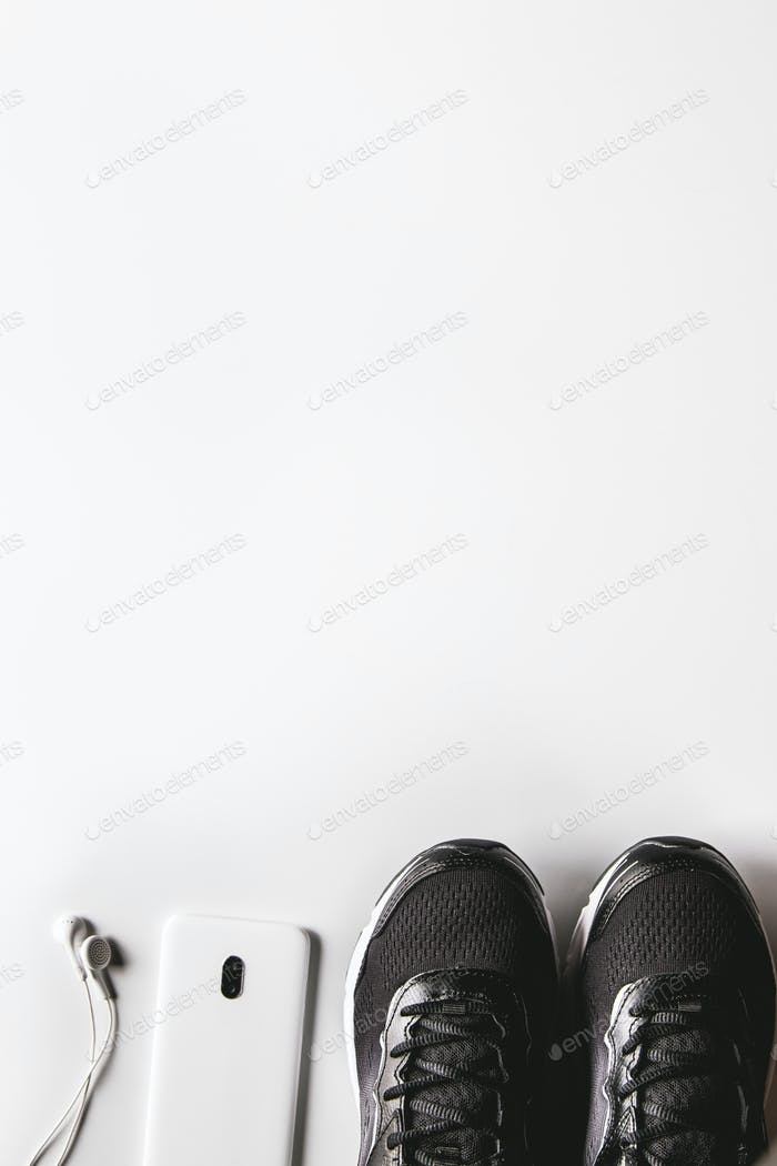 Mockup mobile cellphone with earphone and running shoes on white background. Healthy lifestyles