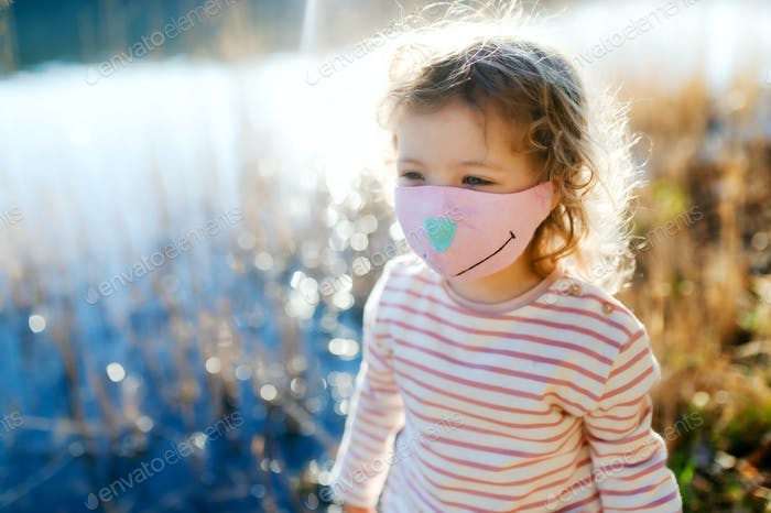 Small girl with face mask outdoors in nature, walking