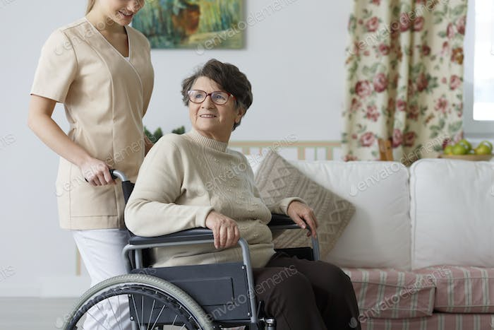 Woman on wheelchair and her nurse