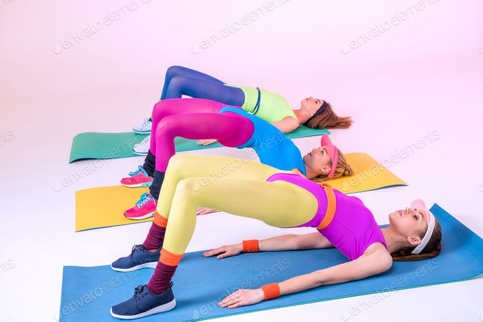 young sporty women doing exercises on training mats