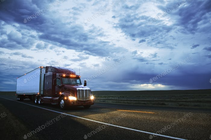 3/4 front view of a commercial truck on the road in the early evening in eastern Washington, USA.