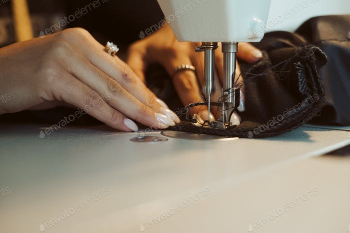 Woman tailor hands working on sewing machine.