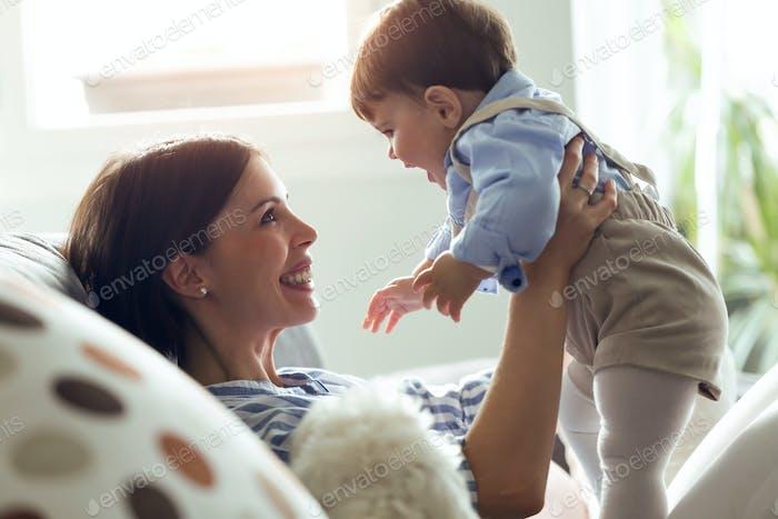 Hübsche junge Mutter mit ihrem Baby spielen und lieben im Wohnzimmer zu Hause.