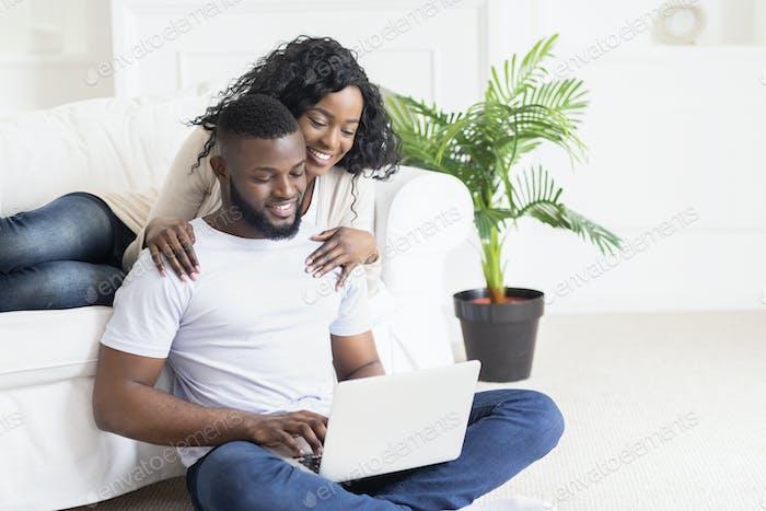 Frau umarmen ihren Mann, der als Freiberufler zu Hause arbeiten