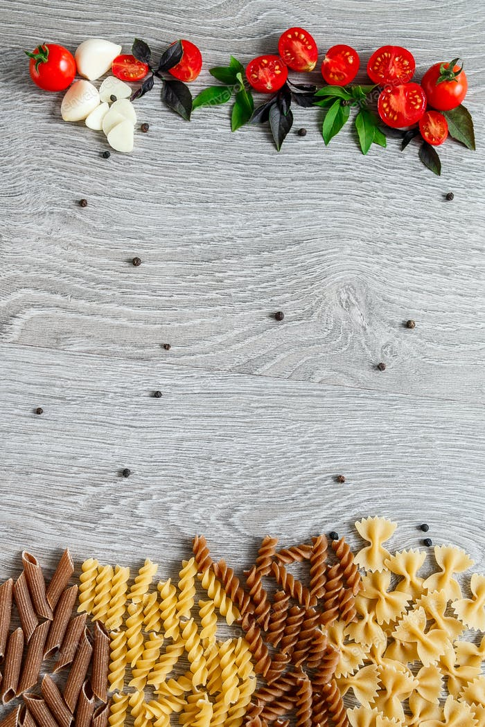 Mixed of two colored pasta near tomatoes, garlic and basil on grey wooden background.