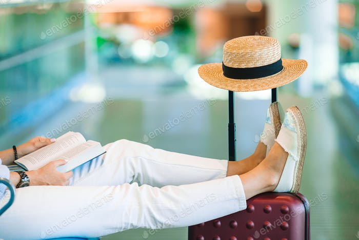 Young woman in an airport lounge waiting for landing. Closeup legs on the baggage