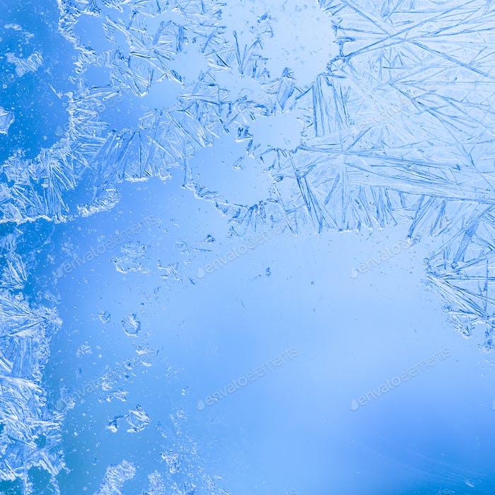 Eiskristalle auf der Innenfläche der Fenster gebildet. Blaue und weiße Farbe. Zuckerguss Fenster Nahaufnahme.