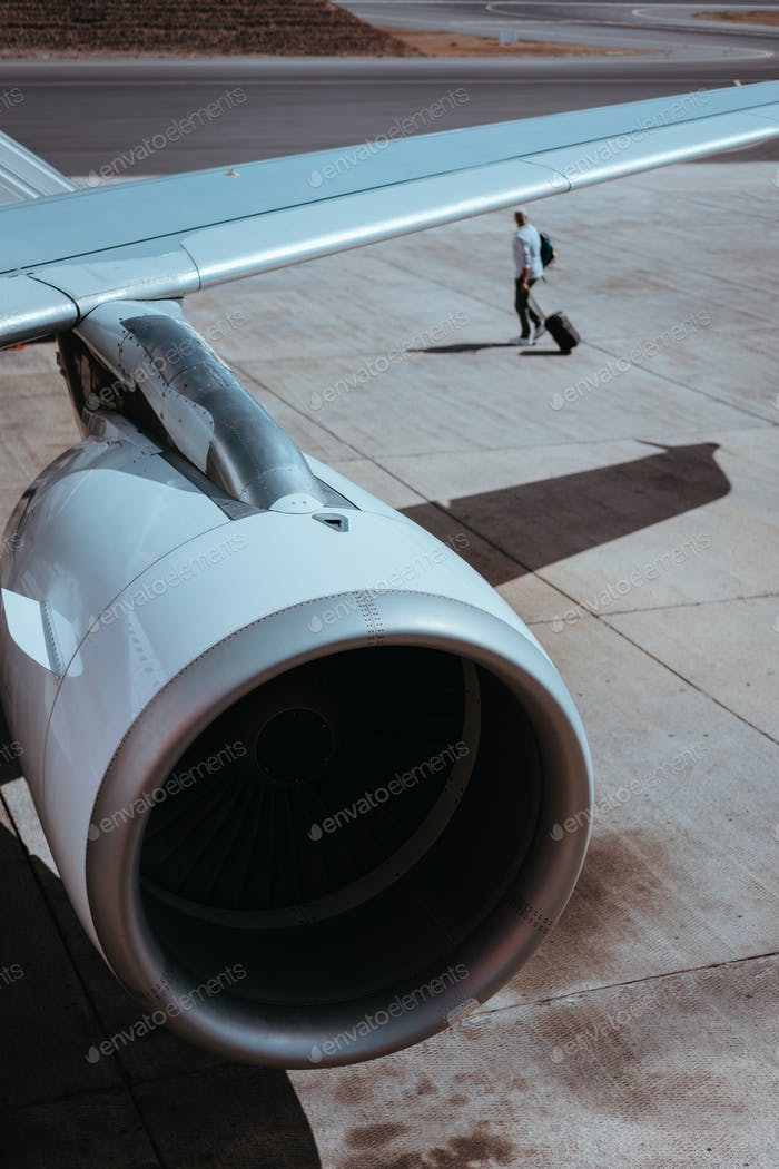 Airplane boarding. Turbine of engine airplane. Traveler with luggege in the background