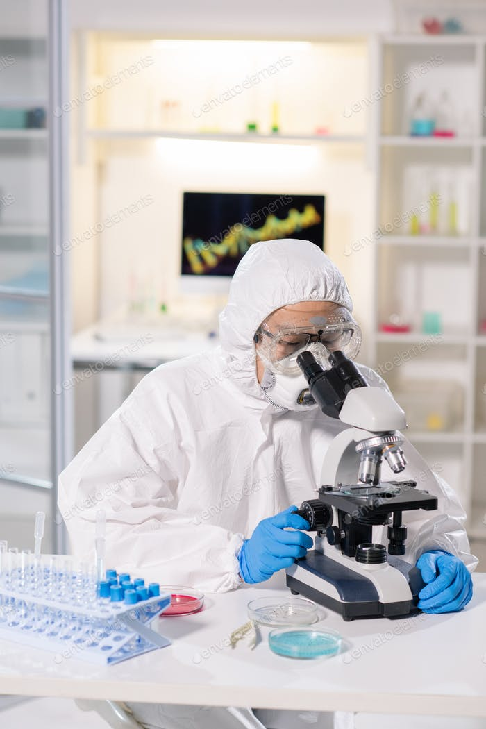 Scientist or chemist in protective workwear sitting at workplace by microscope