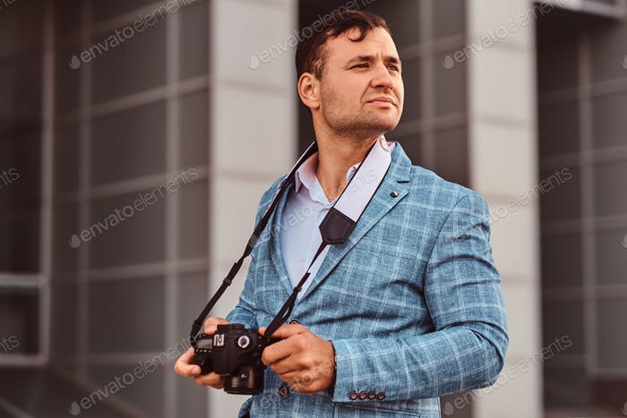 Man with photo camera is standing on the street