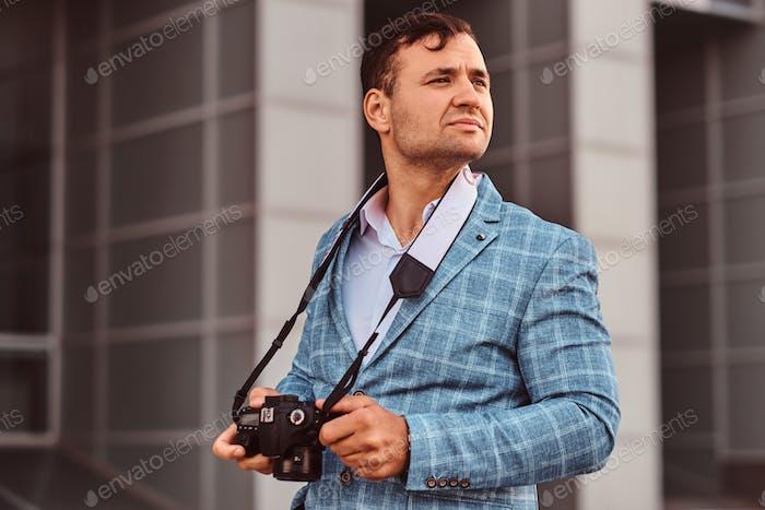 Mann mit Fotokamera steht auf der Straße