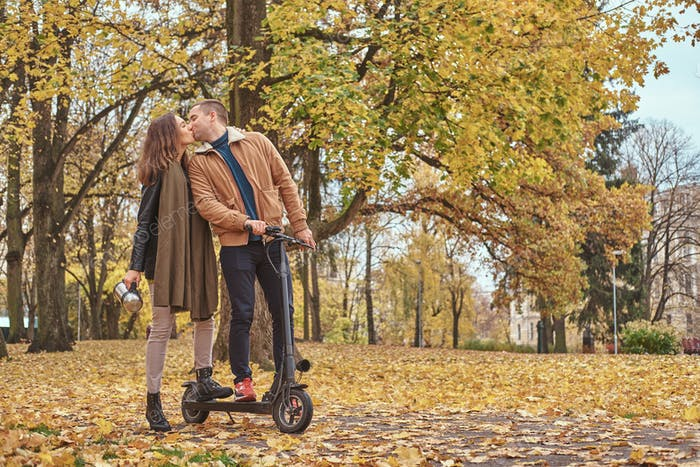 Scooter riding at autumn park