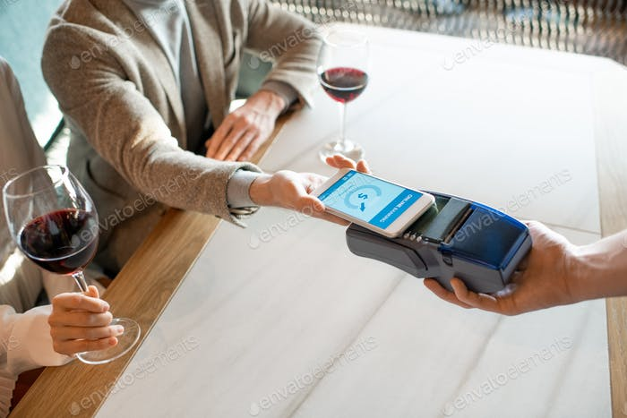 Young man holding smartphone over payment terminal while paying for dinner