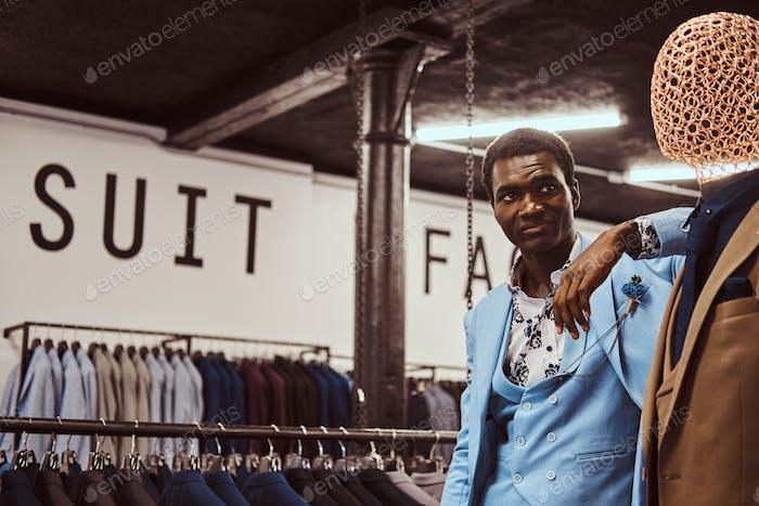 Элегантно одетый афро-американский мужчина опирается на манекен в классическом магазине мужской одежды.