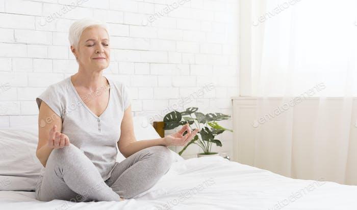 Junge Frau meditiert sitzen in Lotusposition auf dem Bett
