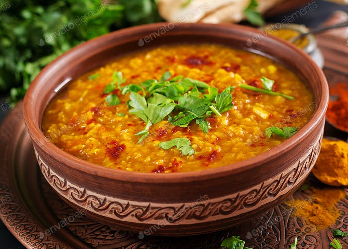 Indian Dhal spicy curry in bowl, spices, herbs, rustic black wooden background.
