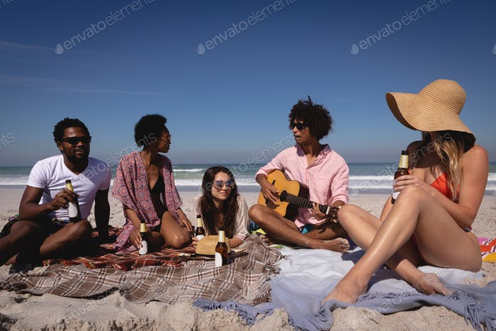 Happy group of friends having fun and drinking beer while sitting on blanket at beach