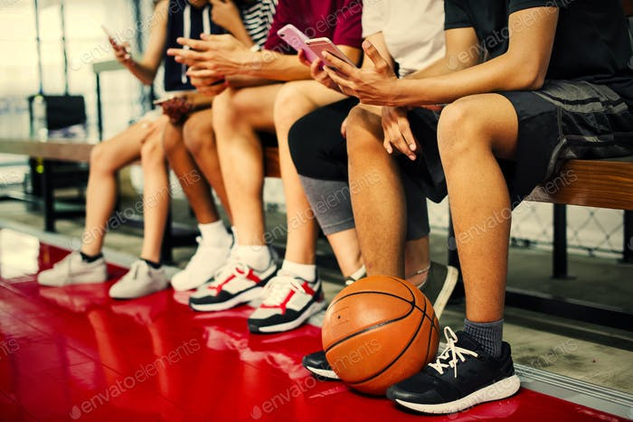Group of young teenager friends on a basketball court relaxing u