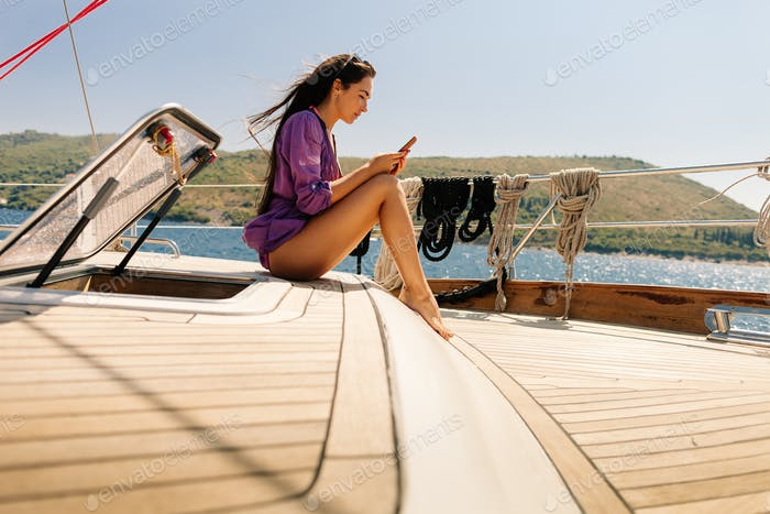 woman travel with smartphone on yacht