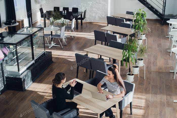 Happy businesswoman talking to businesswoman in office. Two women sitting at table with laptops and