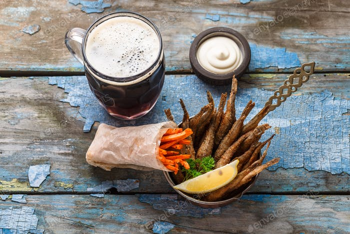 Deep fried fishes with carrots sticks, beer appetizer, copy space