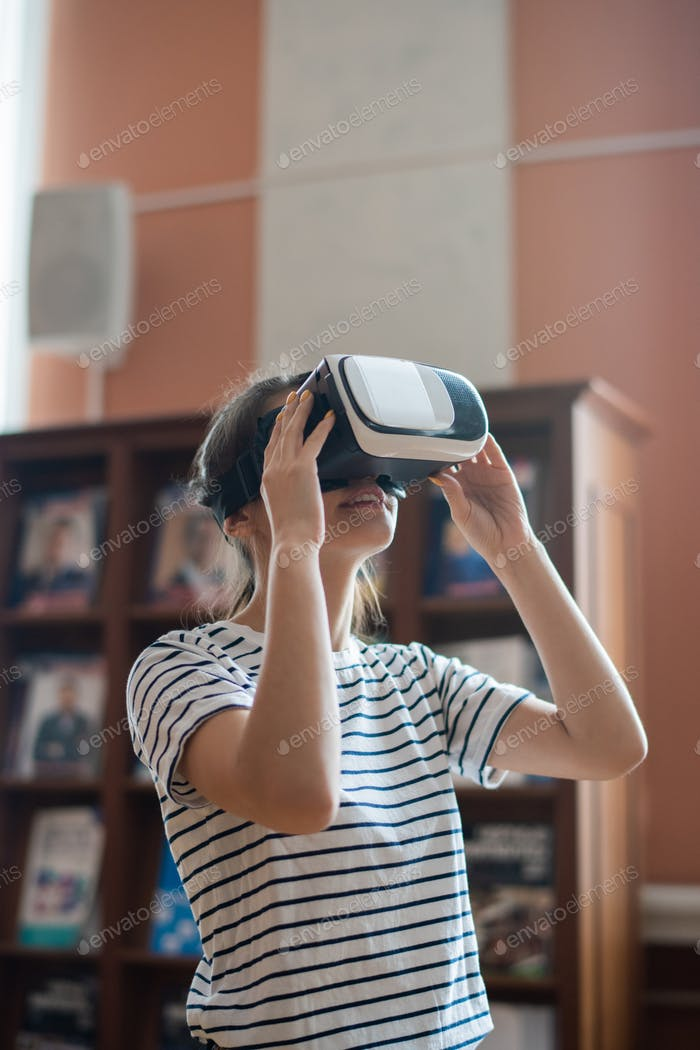 Contemporary teenage girl with vr headset watching 3d movie in library