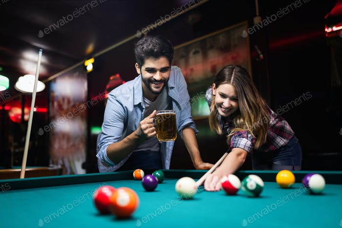 Couple drinking beer and playing snooker on date
