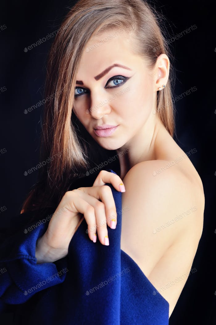 Portrait of a beautiful young woman with long hair on a black ba